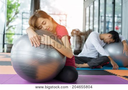 Young asian woman and man fitness exercise aerobics with yoga ball indoor for building muscle slim body and strong Sleeping tired