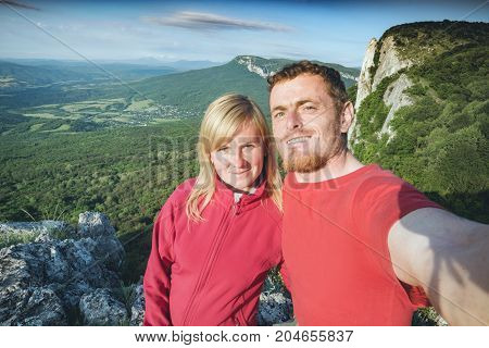 Two hikers making selfie on a mountain valley background. Tourist are laughing and happy.