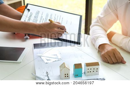 Home business concepts,Home sales brokers sign contracts to sign customers,House plans house model and tablet placed on the table.