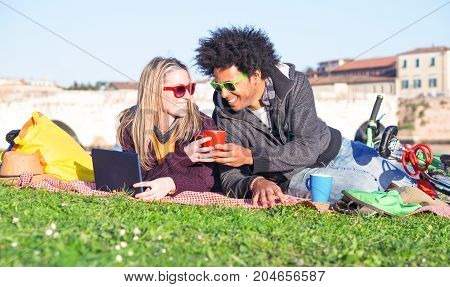 Young interracial couple with pc drinking coffee lying on grass at park in middle season clothing - Afro hair man and blond woman holding tea cup looking at each other and smiling on sunny weekend day