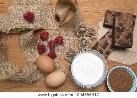Chocolate brownie slices with eggs, flour, raspberries and coco powder.