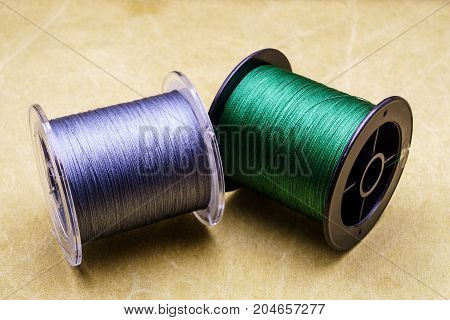 Spools Of Cords On The Background Of Tarpaulin. Green And Gray Fishing Line. Spools Of Braided Fishi