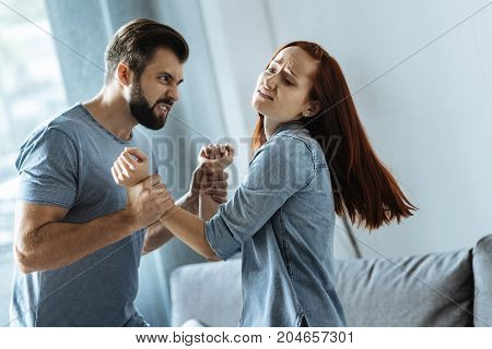 Who is stronger. Furious bearded young man looking at his girlfriend and holding her arms while being ready to hurt her
