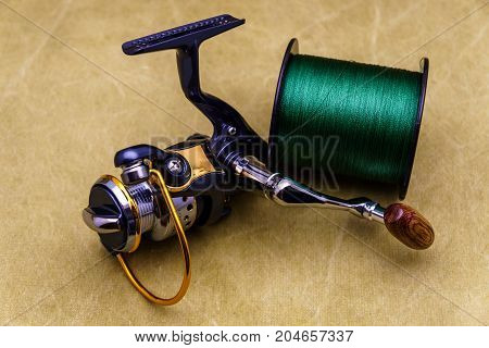 Fishing Reel And Spool Of Cord On The Background Of Tarpaulin. Green  Fishing Line. Fishing Reel And
