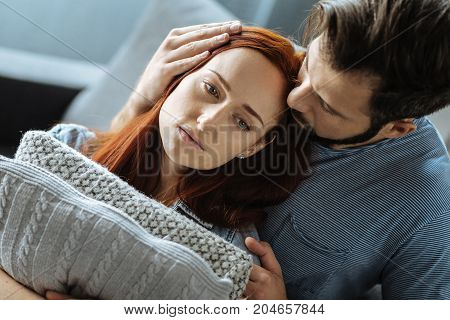 Care and love. Nice handsome loving man hugging his girlfriend and kissing her while trying to comfort her