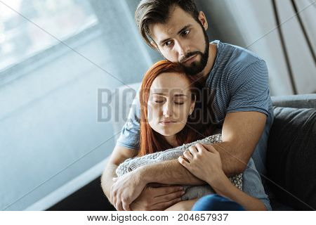 I feel safe. Nice pleasant peaceful woman sitting on the sofa and holding a cushion while being hugged by her boyfriend