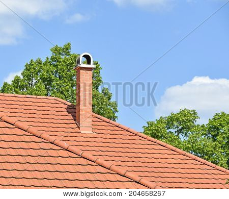 House roof with smoke stack and green trees