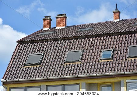 Large house roof with smoke stacks on it