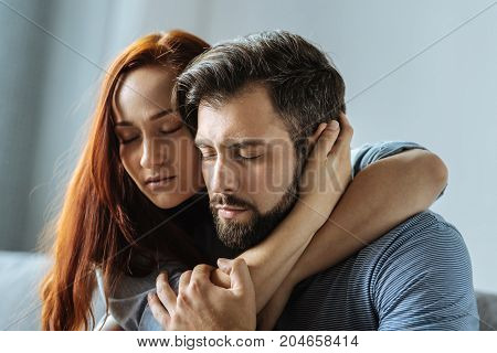 Care and support. Pleasant nice loving couple hugging each other and closing their eyes while showing mutual support