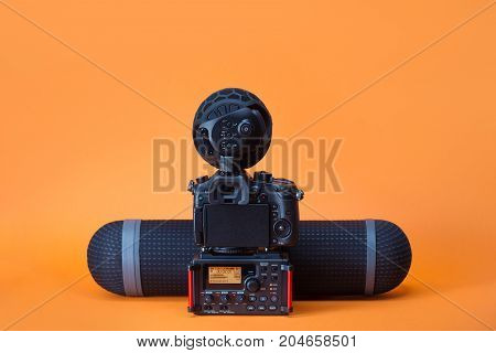 equipment for field video production camera boom mic and audio recorder on the orange background