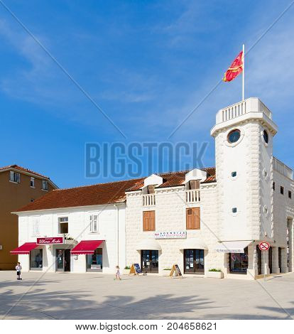 TIVAT MONTENEGRO - SEPTEMBER 10 2017: Unknown children play near Clock Tower (Sat Kula) on Culture Square in popular resort town of Tivat Montenegro