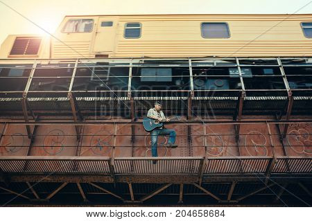 Bluesman with the guitar standing under a bridge on the background of a moving train.
