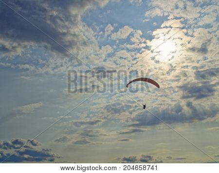 The paraglider flies against the background of the setting sun