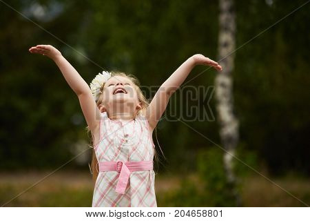 Young smilimg girl hands up. Happy. Outdoors.