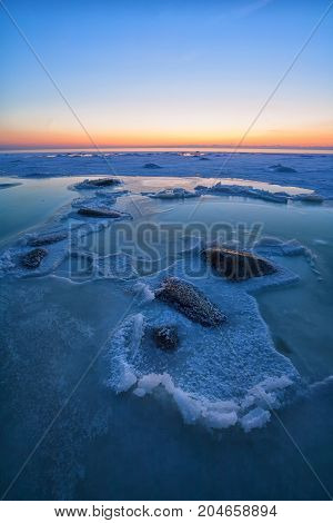 Large stones in the blue ice of the Baltic Sea at winter sunset