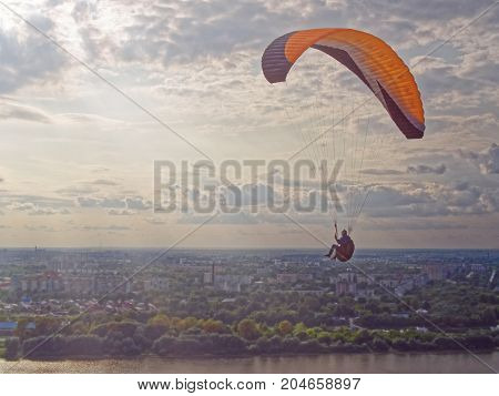 The paraglider flies over the river against the background of the evening sky. In the distance can be seen the industrial district of the city