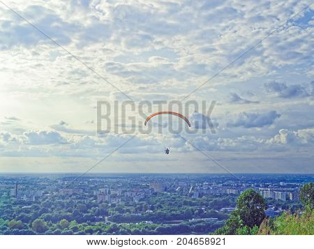 The paraglider flies against the background of the evening sky. In the distance can be seen the industrial district of the city