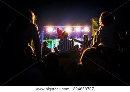 Children who sit on the shoulders of adult parents and waving their hands in the direction of the scene at a concert of a pop star. Shooting a night concert light directly into the camera.