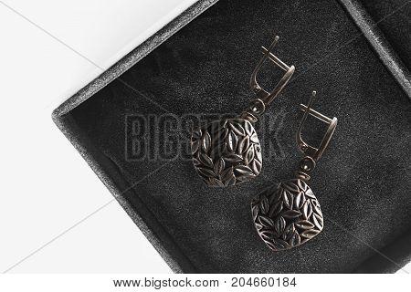 Pair of elegant bronze earrings in black jewel box closeup