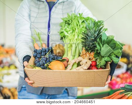 Fruit seller woman with different fruits and vegetables in shop - Worker preparing fruit ecological paper basket - Vegetarian and vegan concept - Focus on right female hand - Warm filter