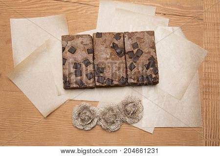 Chocolate brownie slices with hessian flowers on a wooden background