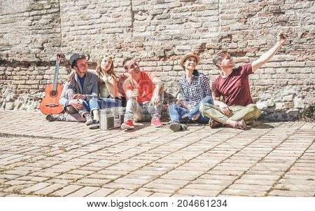 Group of trendy friends taking selfie with mobile cell phone in old historical town center outdoor - Technology mania of new generation concept - Young people having fun - Main focus on right guys
