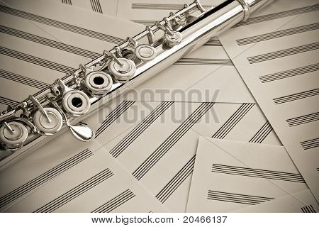 Flute upper middle joint shot with blank music sheets. poster