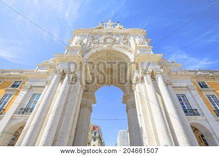 Prospective view of Rua Augusta Triumphal Arch in Commerce Square or Praca do Comercio. Rua Augusta Arch is a stone historic building and visitor attraction in Lisbon, Baixa District, Portugal.