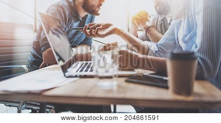 Brainstorming process at office.Young coworkers work together modern office studio.Young people making conversation at wooden table.Horizontal wide.Blurred background