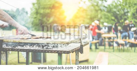 Man cooking bbq meat at festival outdoor - Chef grilling sausages in park outside for picnic - Concept of summer party with families and friends - Warm filter - Focus on hand tongs - Warm filter