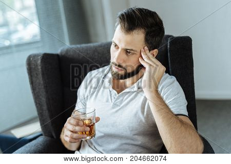 Male drink. Sad cheerless upset man sitting at home and drinking alcohol while thinking about his life