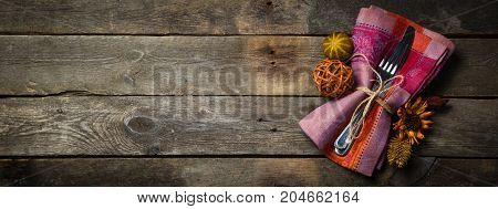Thanksgiving concept - decorations and silver ware on rustic wood background