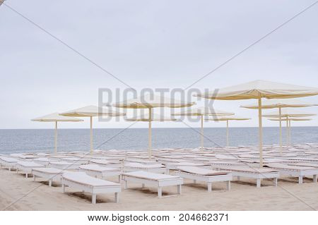 White Chaise Lounges And Umbrellas By The Sea At Dawn, Romantic Time