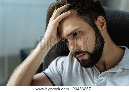 Sadness and depression. Sad cheerless bearded man sitting in the armchair and holding his forehead while feeling frustrated