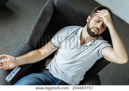I need my medicine. Unhappy depressed sad man holding his forehead and suffering from strong pain while having pills in his hand