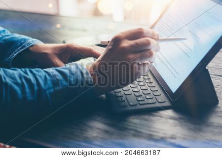 Man working at office.Closeup view of male hands typing on electronic tablet keyboard-dock station. Business text information on device screen. Horizontal, flares effect