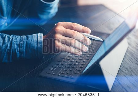Man working at office.Businessman using electronic tablet keyboard-dock station. Pointing on device screen. Horizontal side-view