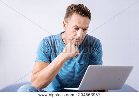 Interesting content. Serious handsome man sitting on the bed, holding the laptop and reading from it, while resting his chin on the hand and seeming concentrated