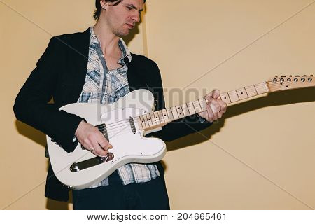 Enthusiastic guitarist playing electric guitar. Creative hobby for adult men, music concept