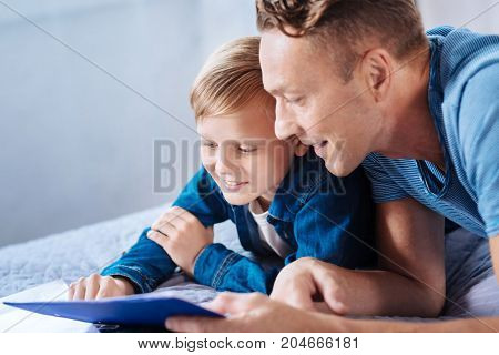 Engaged in reading. Charming little boy lying on the bed next to his smiling father and reading from the printouts together with him