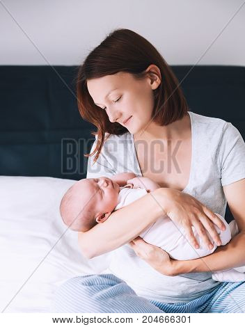 Сaring and loving mother looking on her baby. Sleeping newborn baby in the hands of his mother. Image of happy maternity and family. Mom and child's first month of life at home. poster