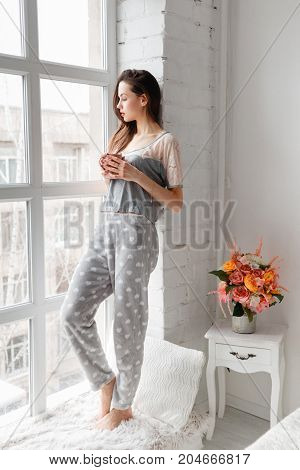Sensual young woman staying on sill near panoramic window at home with cup of coffee. Thoughtfulness and calmness, relaxation and perception concept. Good start of the day