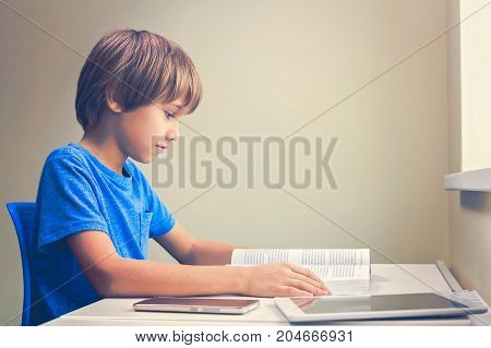 Focused boy reading a book. Tablet computer and mobile phone near to him at the table at home