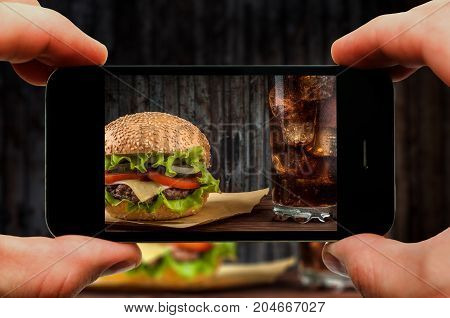 Cheeseburger with cheese on a rustic wooden table. Taking photo of cheeseburger by smartphone. Closeup view of process.