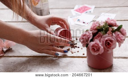 Process of decoration backstage for shooting. Crimson roses and greeting cards on wooden background, congratulation and corresponding photography, close up