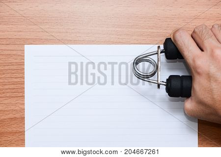 White line paper on brown wooden table and a man hand holding grip top view