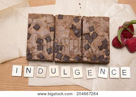 Chocolate brownie slices with raspberries and the word indulgence
