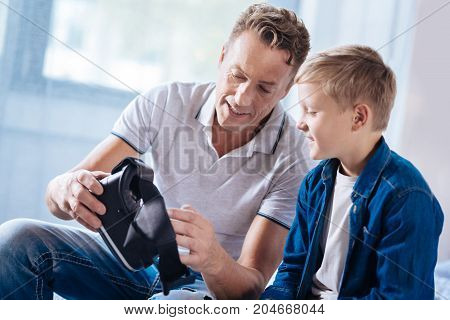 Clear explanation. Cheerful pleasant man sitting next to his son, holding a VR headset and explaining the principles of its work to the boy while he listening attentively