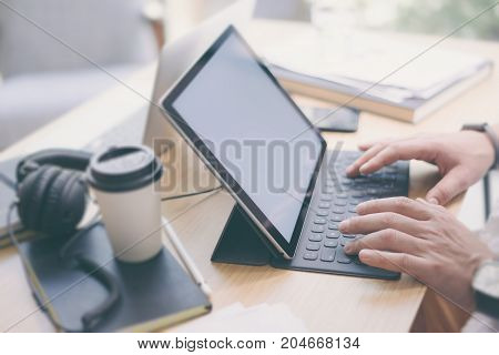 Closeup view of male hands typing on electronic tablet keyboard-dock station.Blogger working at office while sitting at wooden table.Horizontal.Blurred background