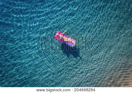 Aerial view of young woman swimming on the pink inflatable mattress in the transparent turquoise sea in Ichmeler, Turkey. Summer seascape with girl, azure water in the morning. Top view from drone